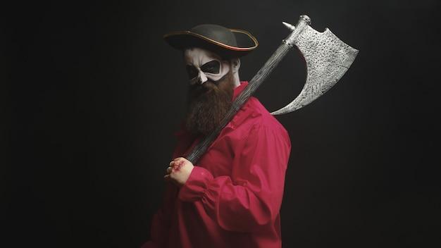 Aterrador hombre barbudo sosteniendo un hacha disfrazado de pirata para halloween.