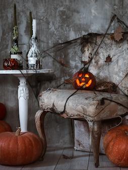 Aterradora composición con la calabaza de jack y velas encendidas, telas de araña y una escoba de bruja en un muro de hormigón