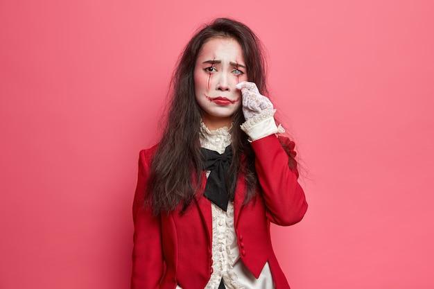 Aterradora mujer morena abatida con maquillaje de halloween enjuga lágrimas tiene expresión sombría el arte de la cara ensangrentada usa chaqueta roja y guantes de encaje lente blanca en poses de ojos en el interior contra la pared rosada