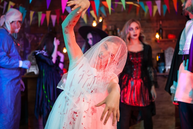 Aterradora niña espeluznante en ropa de novia con maquillaje de halloween en vestido de deshierbe. doctor loco en segundo plano.