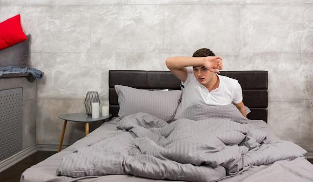 Aterrorizado joven se despertó de una pesadilla y se secó el sudor de la frente mientras estaba sentado en una elegante cama con colores grises en un dormitorio estilo loft