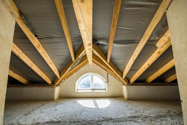 Ático de un edificio con vigas de madera de una estructura de techo y una pequeña ventana.
