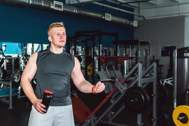 Atleta aclama a alguien fuera de la pantalla en el gimnasio sosteniendo una botella agitadora para nutrición deportiva en la mano