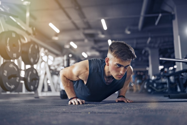 Atleta adulto joven haciendo flexiones como parte del entrenamiento de culturismo.