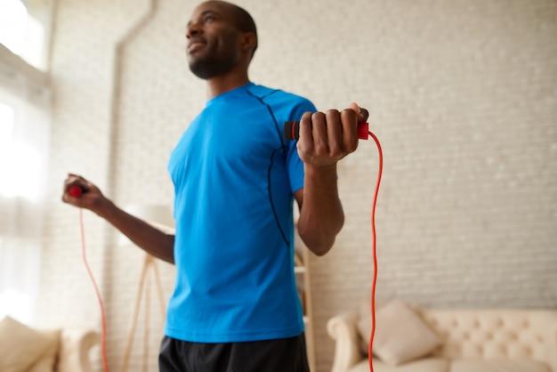 Atleta africano haciendo ejercicios con saltar la cuerda en casa.
