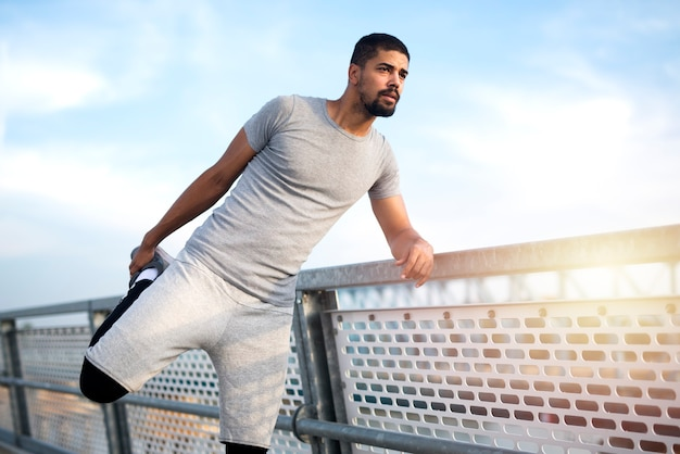 Atleta afroamericano estirando sus piernas antes de correr
