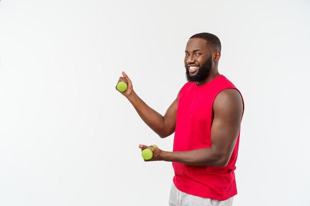 Atleta afroamericano joven holding lifting dumbbells en blanco aislado.