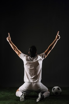 Atleta anónimo apuntando hacia arriba mientras celebra la victoria