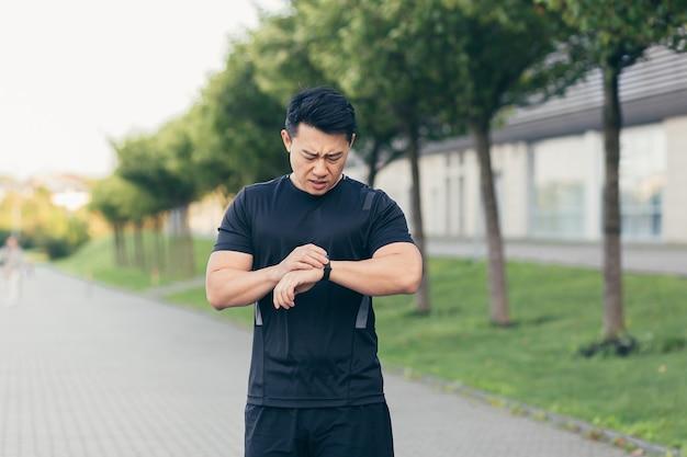 Atleta asiático masculino, cansado después de trotar por la mañana, corre en el parque cerca del estadio