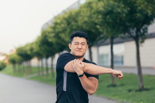 Atleta asiático masculino, dolor de hombro amasado, músculos del brazo doloridos en el parque