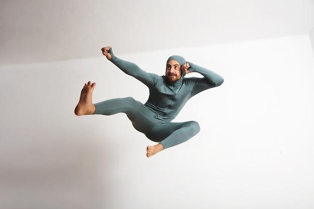 Atleta barbudo joven y equipado con su traje térmico de snowboardint de invierno y divirtiéndose actuando como un ninja, saltando con patadas en el aire