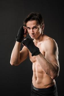 Atleta sin camisa posando en guantes de boxeo