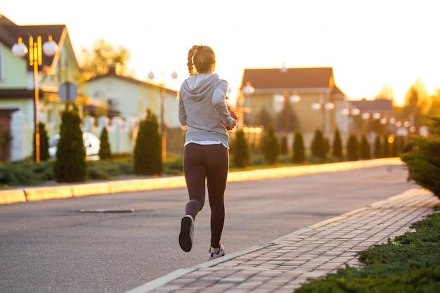 Atleta corredor corriendo en carretera. mujer fitness trotar entrenamiento concepto de bienestar.