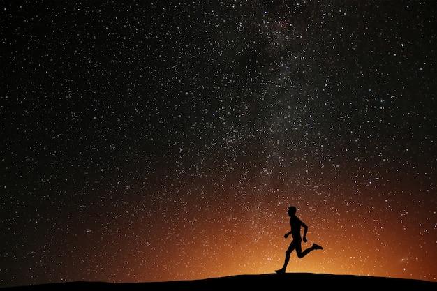 Atleta corredor corriendo en la colina con fondo hermoso noche estrellada. silueta de entrenamiento de jogging de hombre en tiempo oscuro, concepto de bienestar.