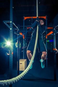 Atleta de crossfit con una cuerda durante el entrenamiento en el gimnasio