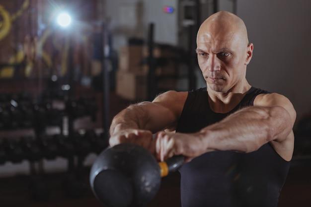 Atleta crossfit maduro ejercicio con pesas rusas