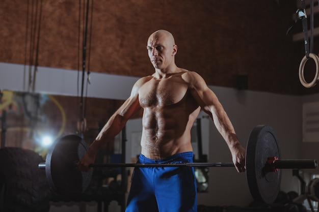 Atleta de crossfit masculino fuerte ejercicio con barra pesada
