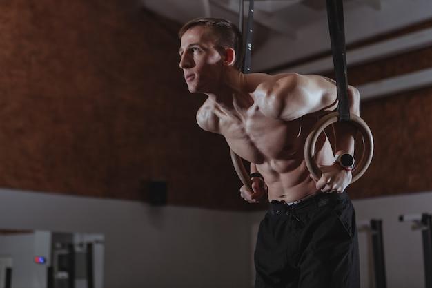Atleta de crossfit masculino musculoso trabajando en anillos de gimnasia