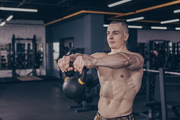 Atleta de crossfit muscular trabajando con pesas rusas