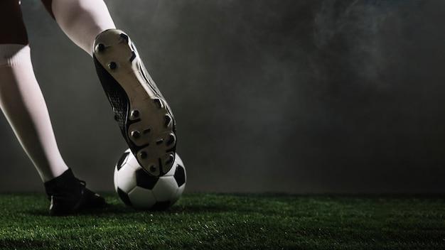 Atleta de cultivos pateando el balón de fútbol