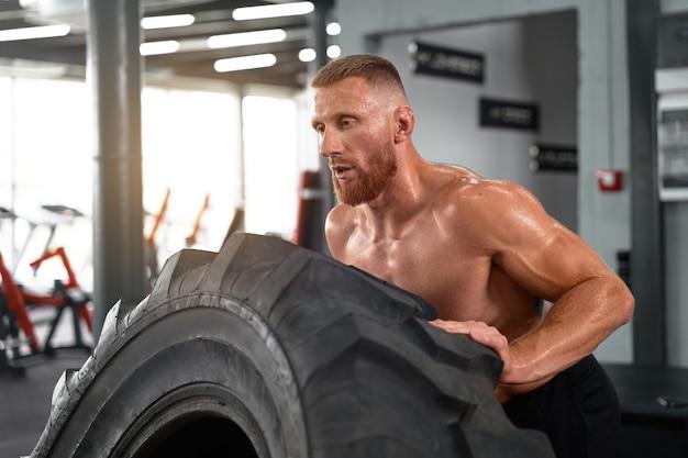 Atleta deportivo hombre ascensor rueda gimnasio