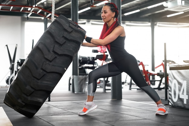 Atleta deportivo mujer rueda de elevación gimnasio
