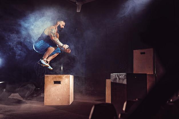 El atleta dio ejercicio. saltando sobre la caja. fase de aterrizaje. fotos de gimnasio en el tono oscuro. fumar.