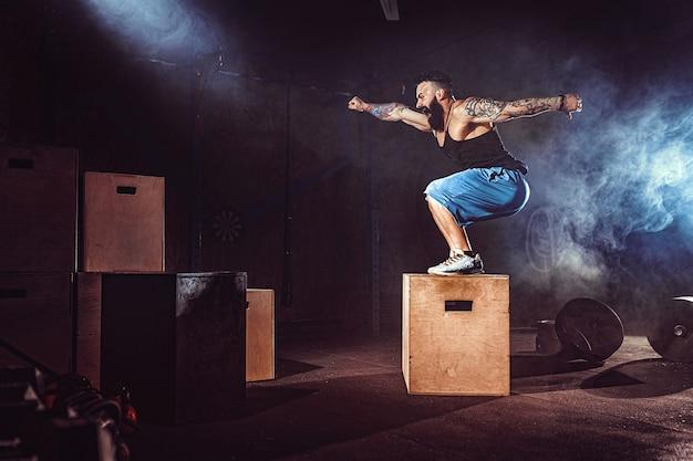 El atleta dio ejercicio. saltando sobre la caja. fase de aterrizaje.