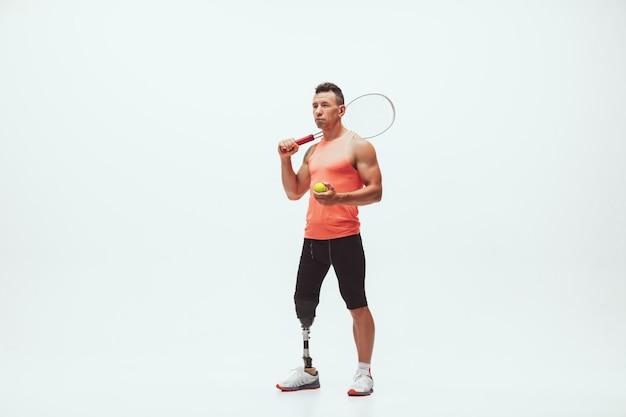 Atleta con discapacidad o amputado aislado en blanco. tenista profesional masculino con entrenamiento de prótesis de pierna