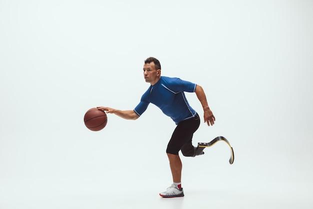 Atleta con discapacidad o amputado aislado en el espacio de estudio blanco. jugador de baloncesto profesional masculino con prótesis de pierna entrenando y practicando en estudio.