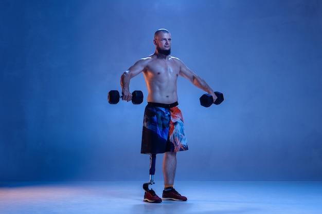 Atleta con discapacidad o amputado aislado en pared azul.