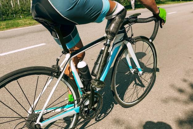 Atleta con discapacidad o amputado entrenando en ciclismo en un día soleado de verano. deportista masculino profesional con prótesis de pierna practicando al aire libre. deporte para discapacitados y concepto de estilo de vida saludable.