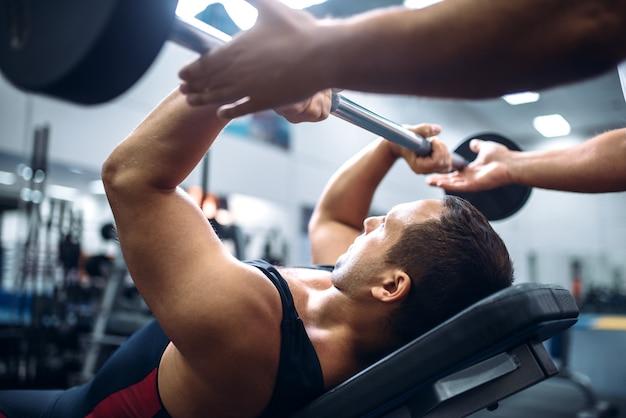 El atleta se encuentra en un banco, ejercicio con barra