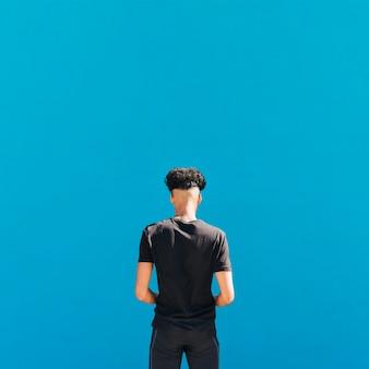 Atleta étnico en ropa deportiva negra sobre fondo azul