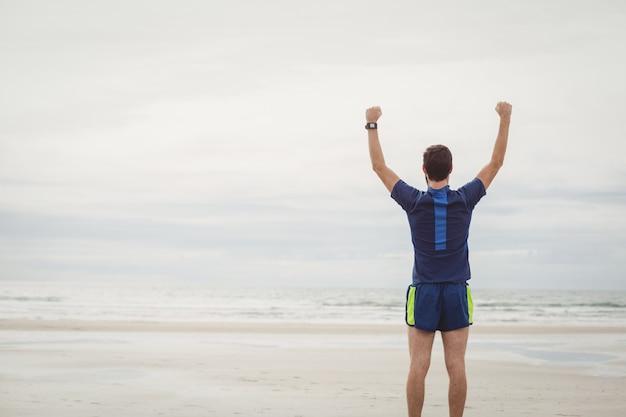 Atleta feliz de pie en la playa con las manos levantadas