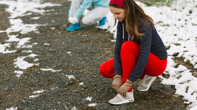 Atleta femenina atar cordones de los zapatos