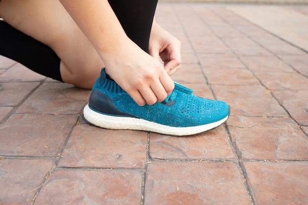 Atleta femenina atar sus zapatos prepararse para correr al aire libre