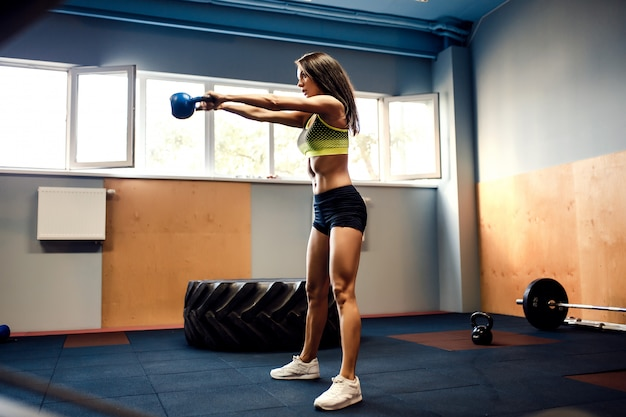 Atleta femenina atractiva realizando un swing de caldera-campana