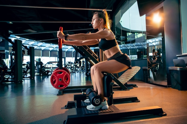 La atleta femenina entrenando duro en el gimnasio fitness y concepto de vida saludable