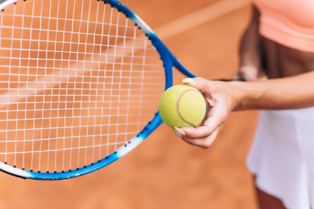 Atleta femenina golpea una pelota de tenis con una raqueta