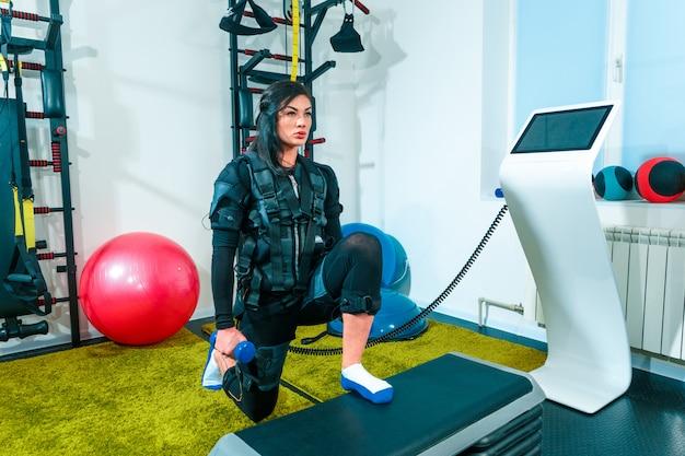 La atleta femenina haciendo ejercicio en un gimnasio ems