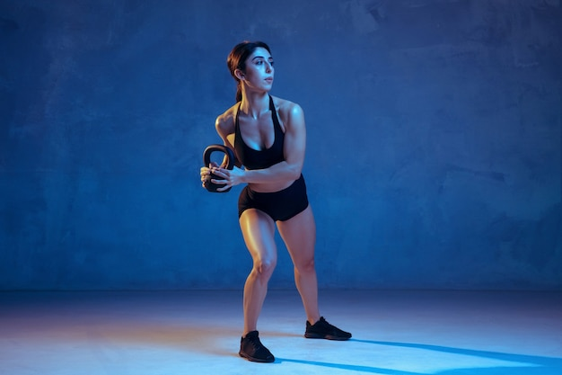 Atleta femenina joven caucásica practicando en azul