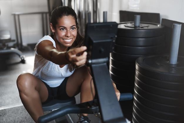 Atleta femenina joven motivada, sonriendo en el gimnasio, usando equipo de prensa de piernas