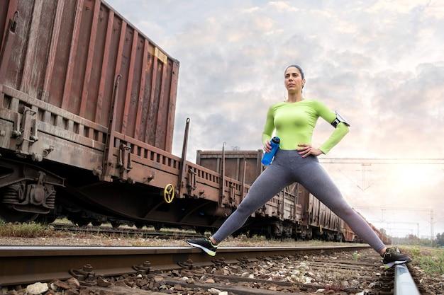 Atleta femenina motivándose y estirando su cuerpo sobre las vías del tren antes de entrenar.