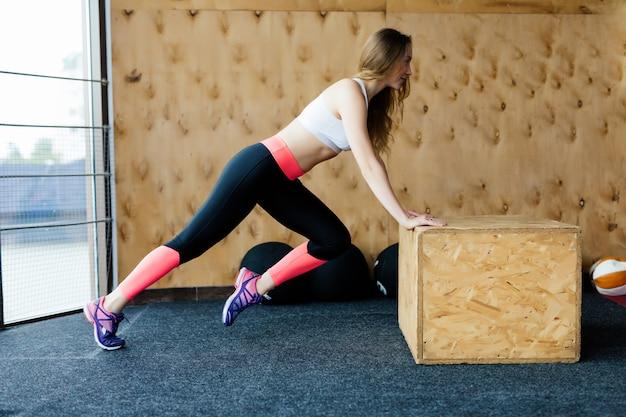 Atleta femenina practicando flexiones y burpees en el gimnasio