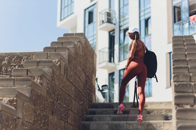 Atleta femenina sudando después de subir escaleras, correr y hacer ejercicio al aire libre