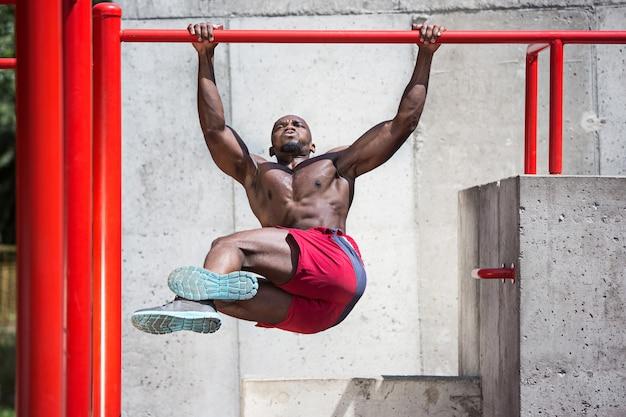 El atleta en forma haciendo ejercicios en el estadio.