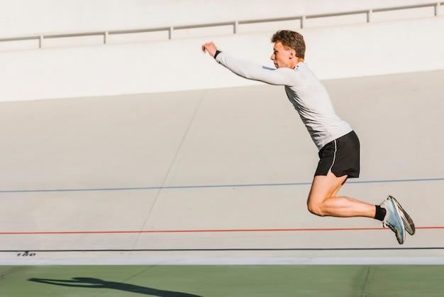 Atleta haciendo un salto de longitud con copia espacio.