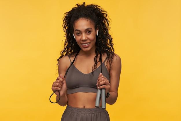 Atleta hermosa joven sonriente con auriculares inalámbricos de pie y sosteniendo la cuerda en el cuello aislado sobre la pared amarilla
