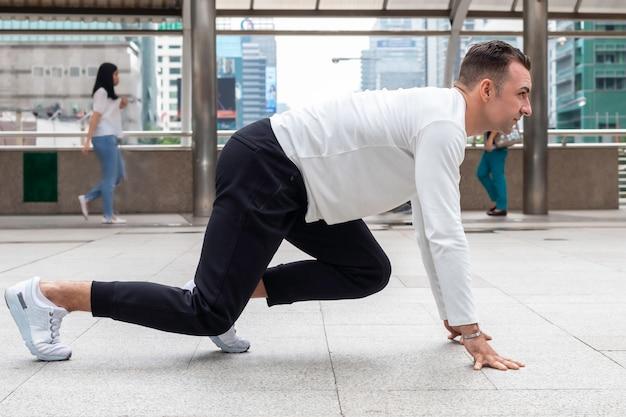Atleta hombre caucásico en ejecución de inicio plantean en la calle de la ciudad.
